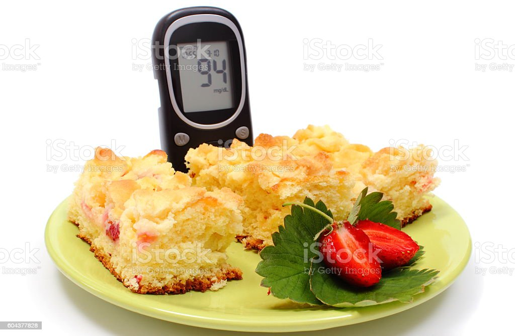 Pieces of yeast cake with strawberries and glucometer stock photo