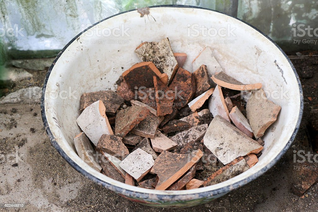 Pieces oof a brown clay pot in a bowl stock photo