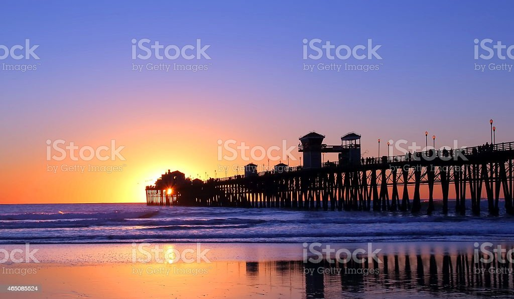 A pier at low tide with sunset behind stock photo