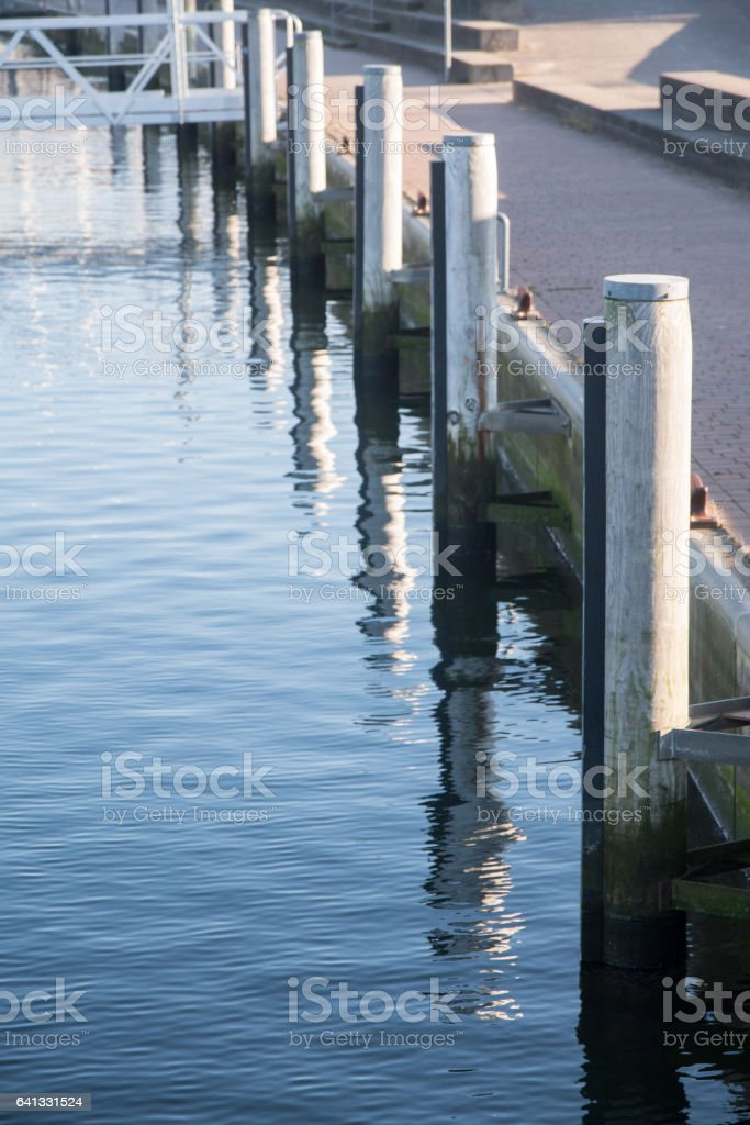 Pier at the marina, wooden bollards and blue sea, vertical stock photo