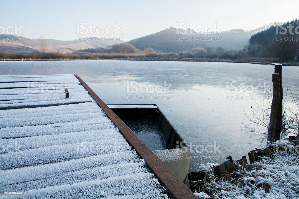 pier, boat and frozen lake in  winter landscape stock photo