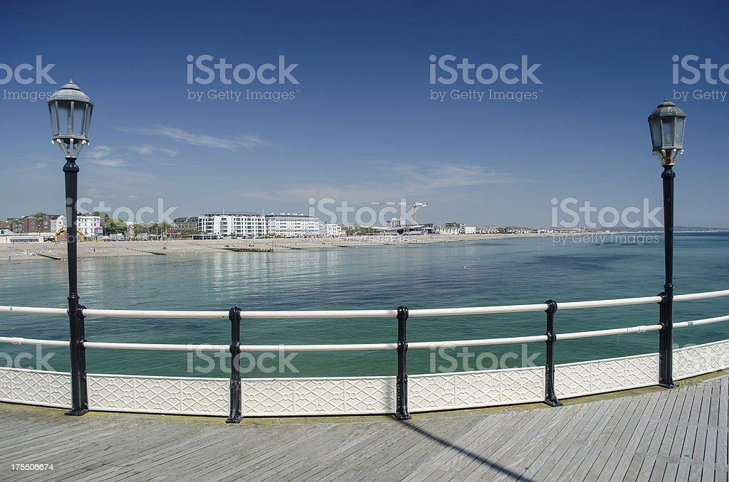 pier deck view of ocean between lamp poles stock photo