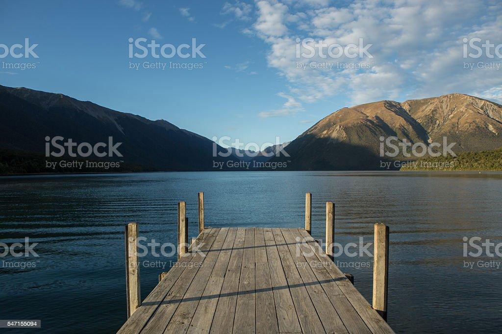 Pier lying on lake Rotoiti, mountain landscape on background stock photo