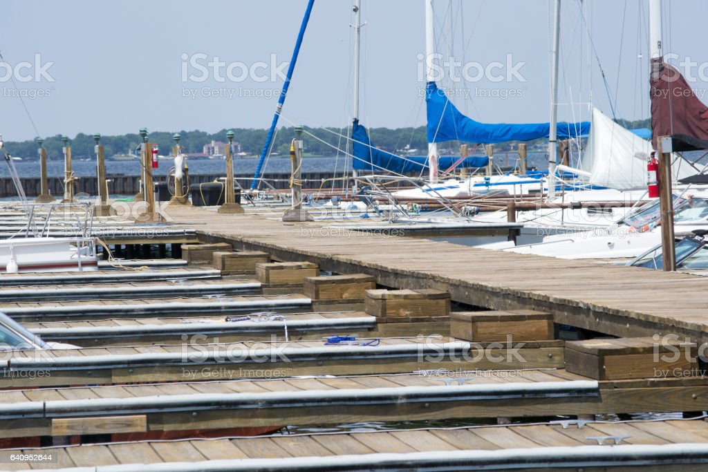 Pier With Boats Docked In Their Slips On A Lake stock photo