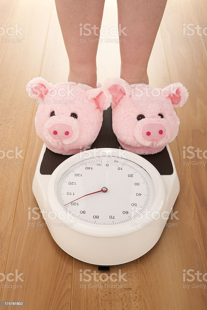Pig slippers on weight scales royalty-free stock photo