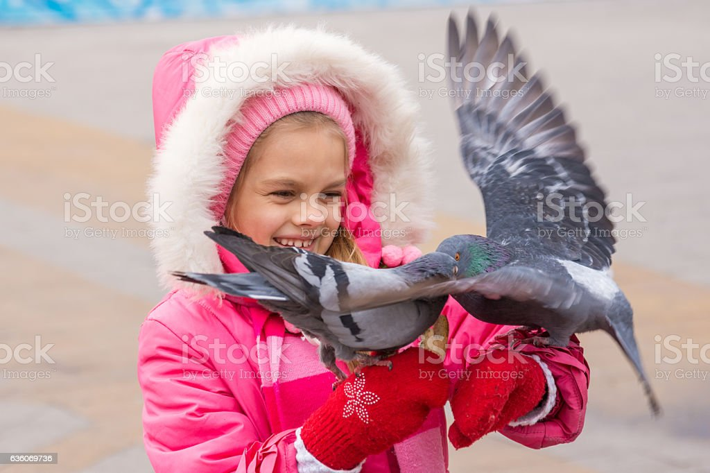 Pigeons fighting for crust of bread in hands of children stock photo