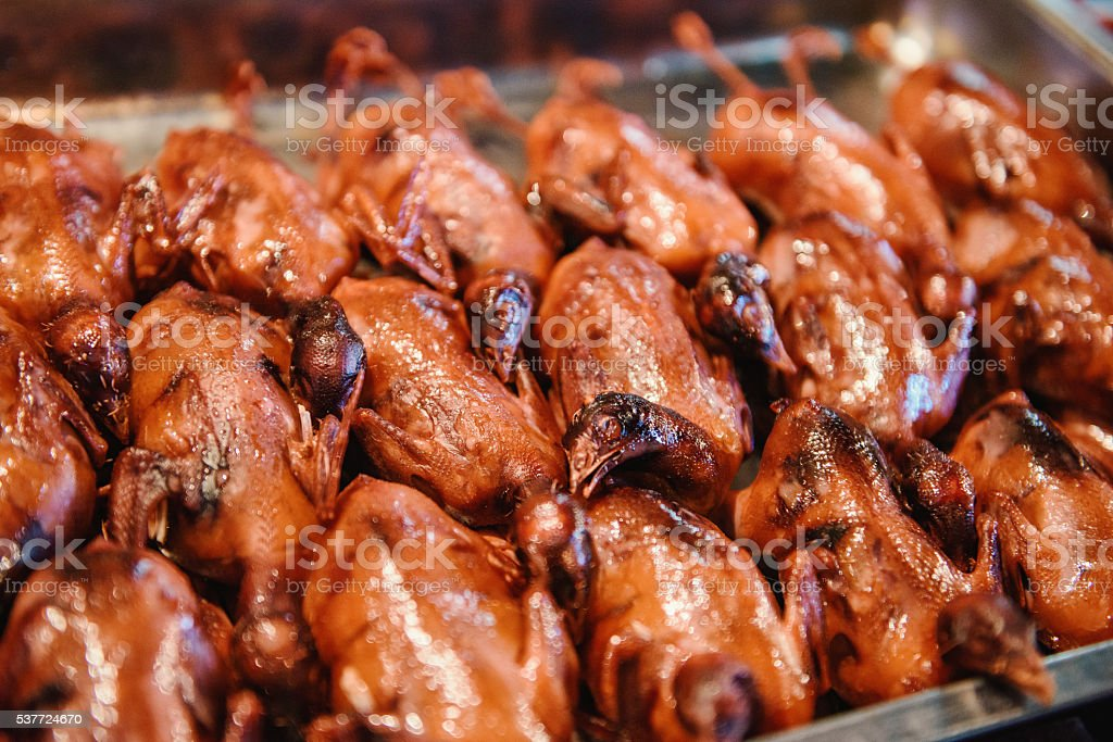 Pigeons on a grill in a chinese food market. stock photo