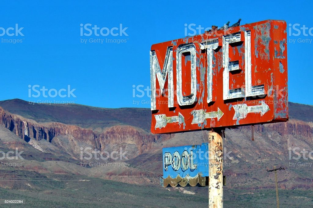 Pigeons Roosting Atop Motel Sign stock photo