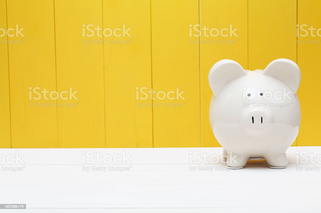 Piggy bank against a yellow wall stock photo