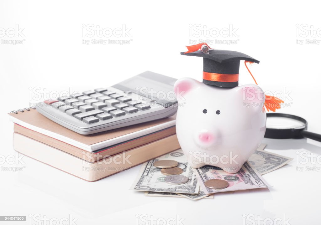 piggy bank and black graduation hat with money, book stock photo