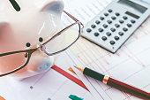 Piggy bank and calculator on business documents background