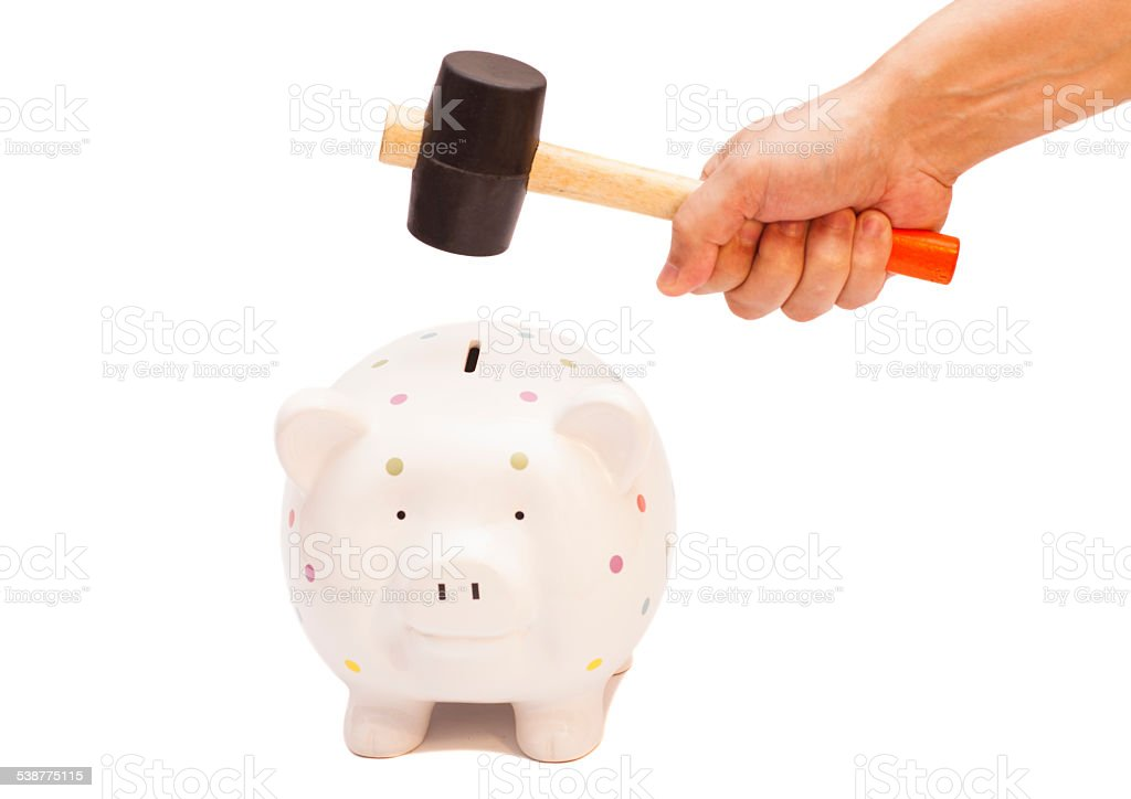 Piggy bank and hand with hammer stock photo
