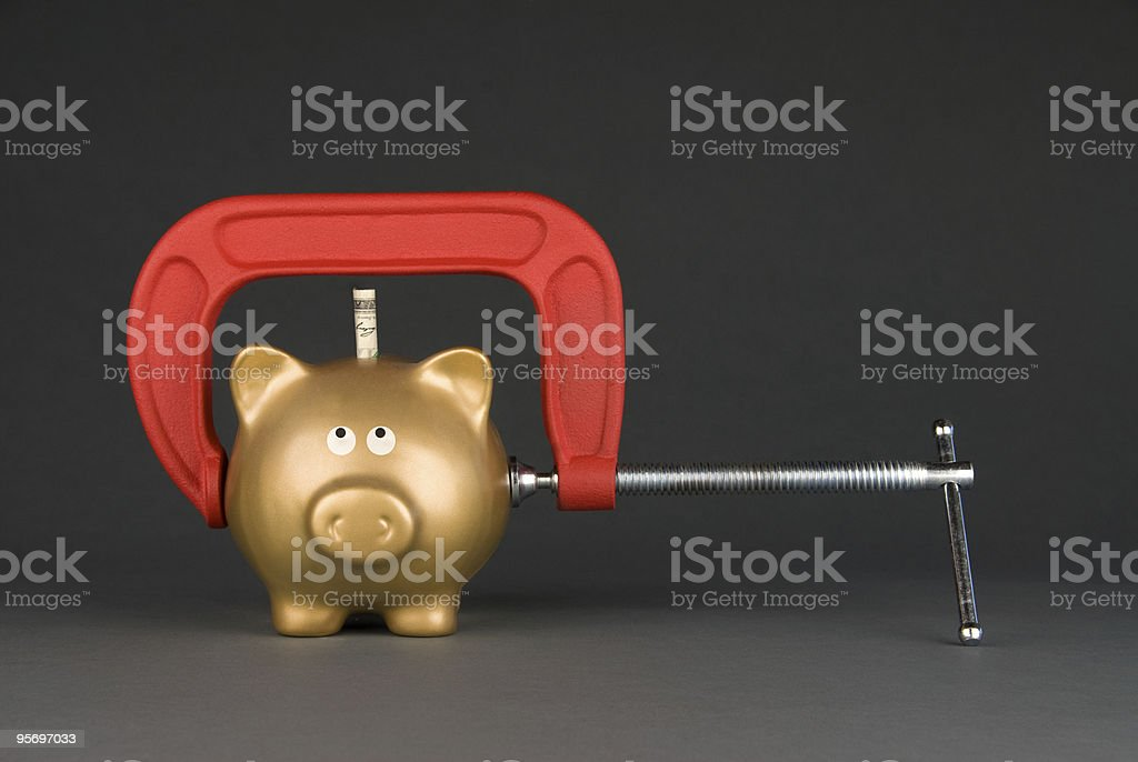 Piggy bank being squeezed stock photo