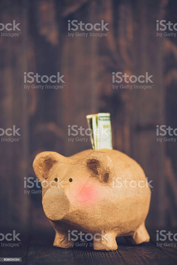 Piggy bank flush with cash against rustic wooden background stock photo