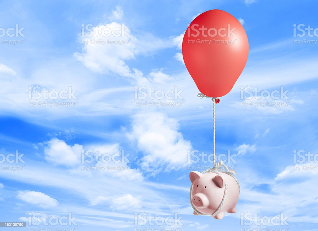 Piggy bank lifted up into sky by inflated balloon stock photo