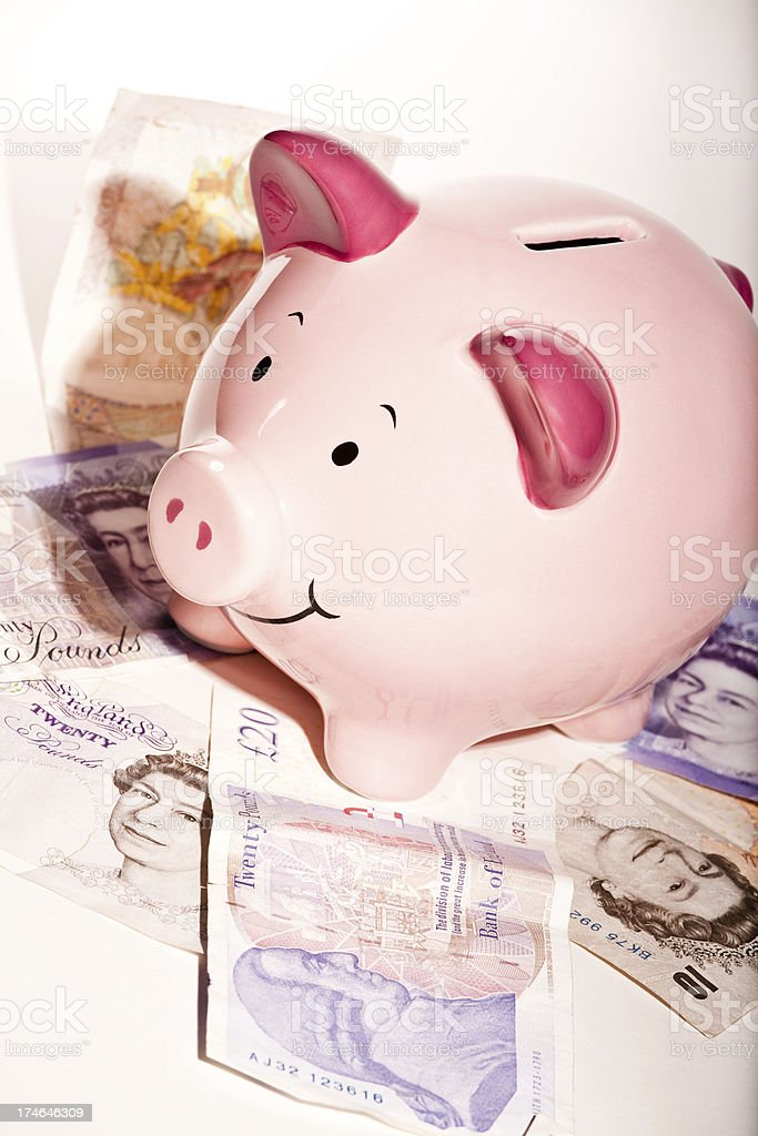 Piggy bank on a pile of cash royalty-free stock photo