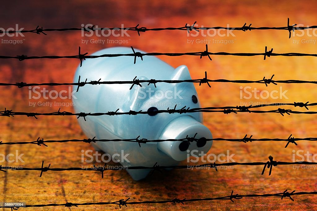 Piggy bank on grunge background against barbwire stock photo