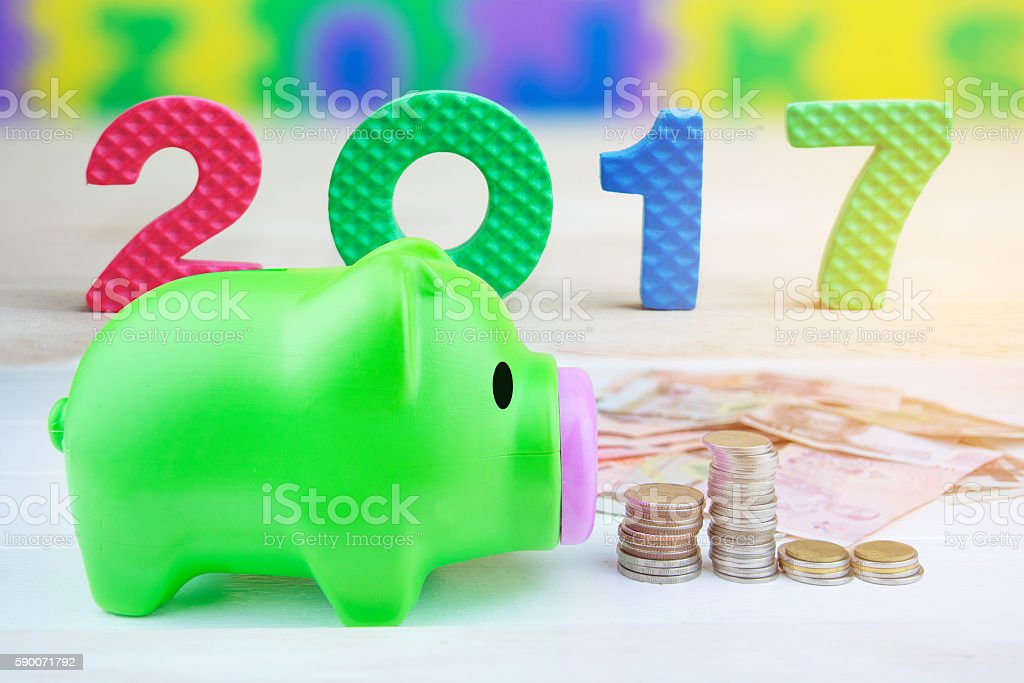 piggy bank on pile of coins(happy new year 2017) stock photo