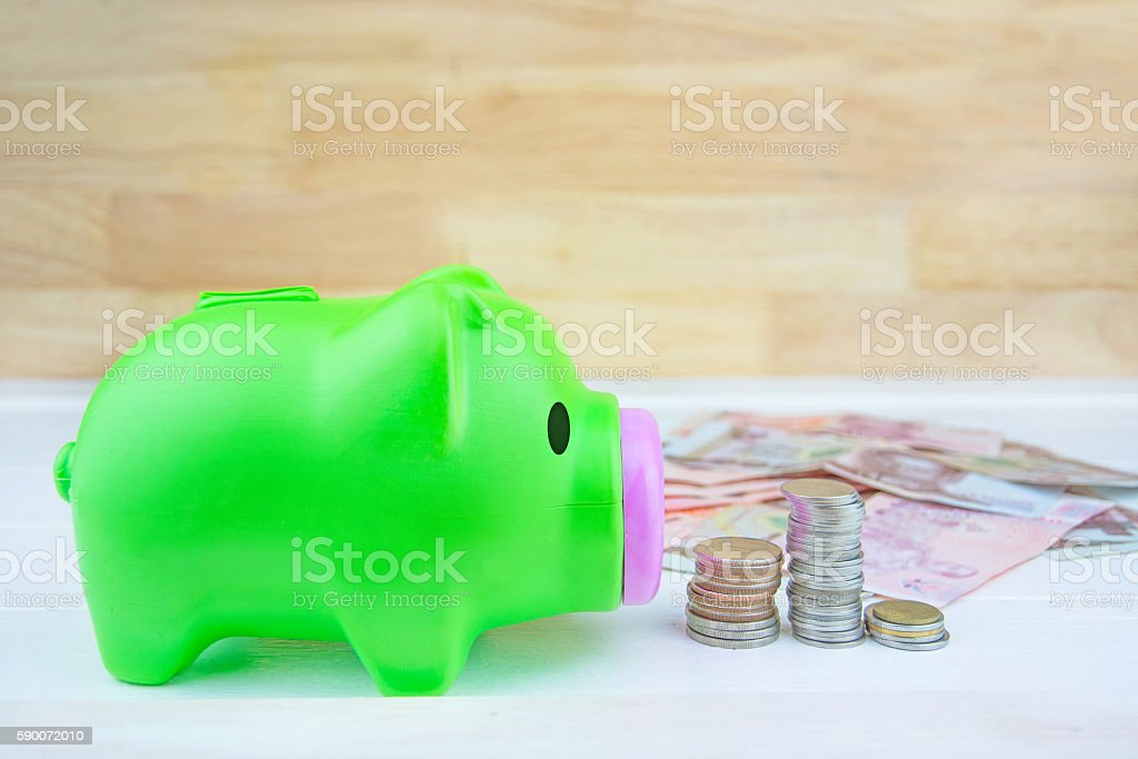 piggy bank on pile of coins with wooden wall. stock photo
