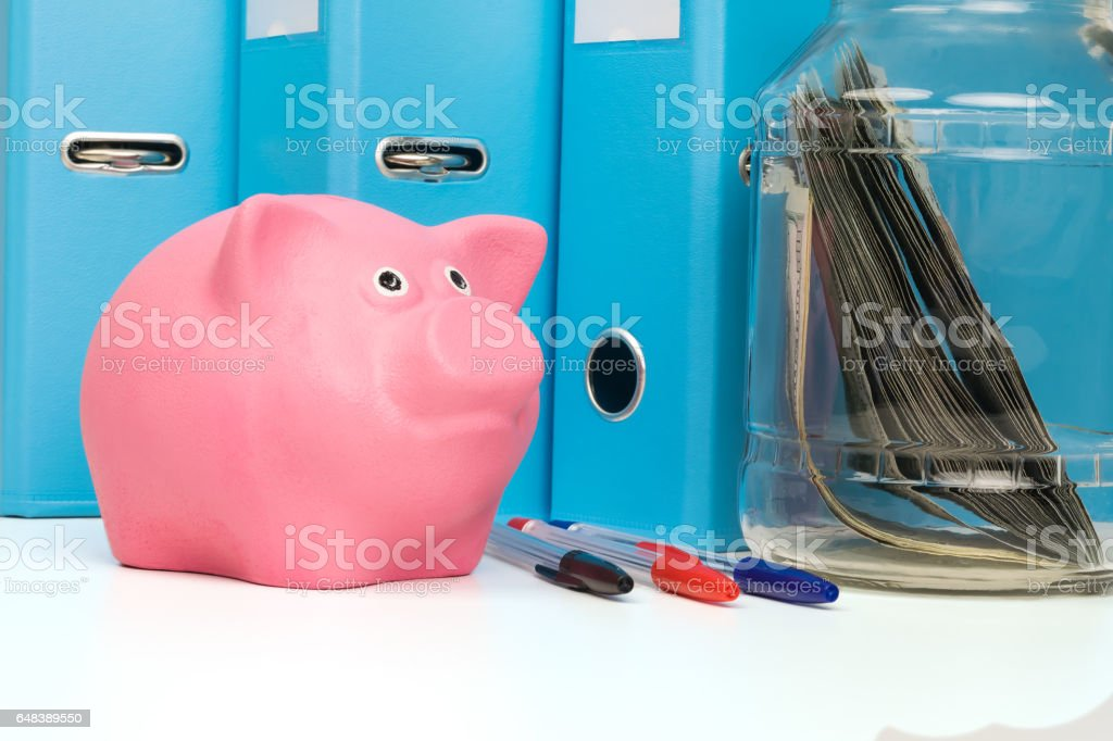piggy bank on the table in front of school subjects stock photo