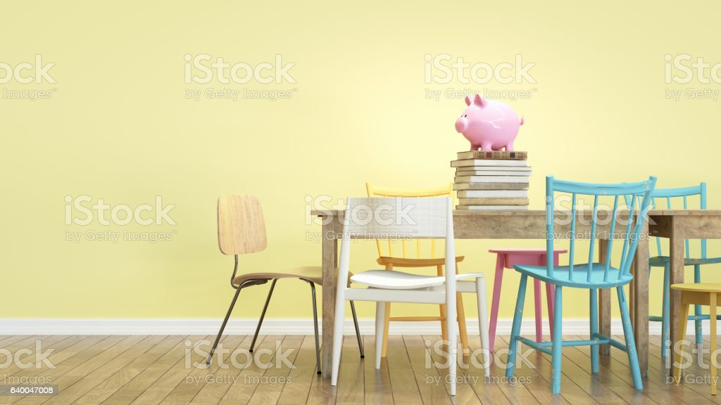 Piggy bank sits on a table with several chairs. stock photo