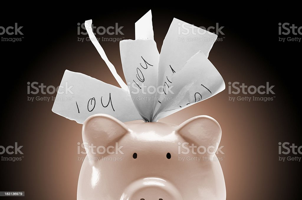 Piggy bank stuffed full of IOU notes on pink background stock photo
