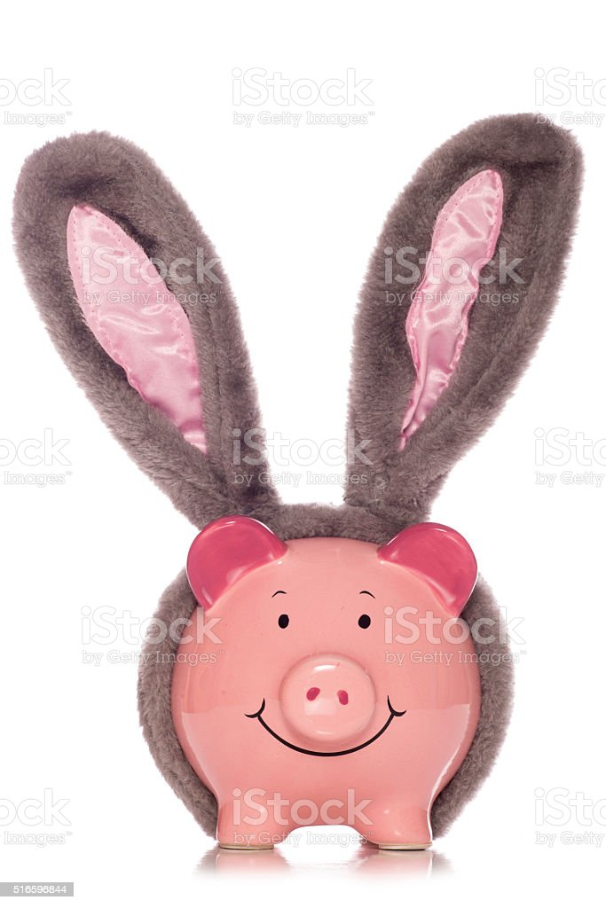 piggy bank wearing easter rabbit ears stock photo