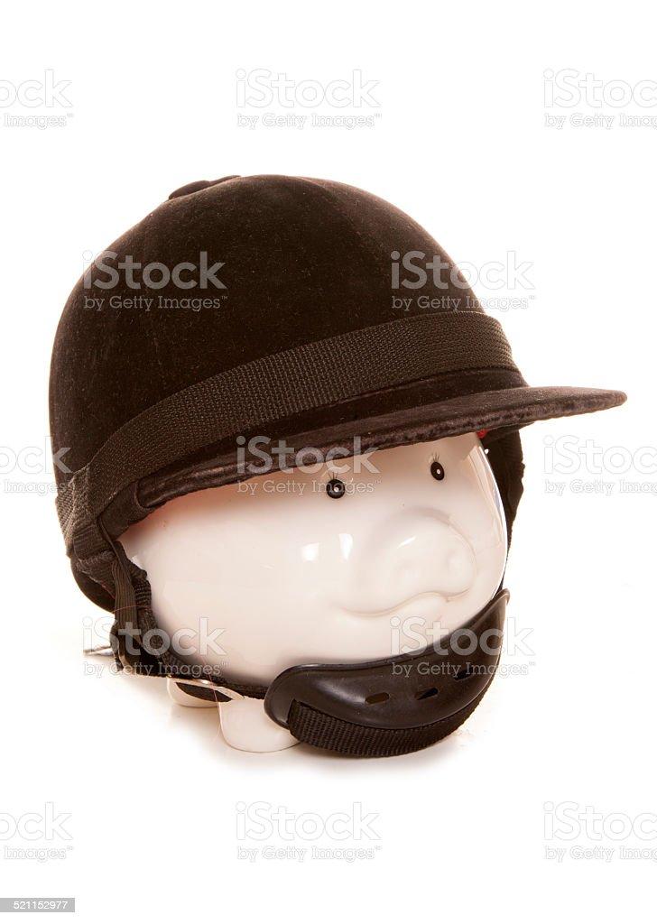 piggy bank wearing horse riding helmet stock photo