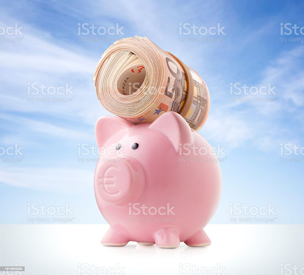Piggy bank with a roll of euro banknotes royalty-free stock photo