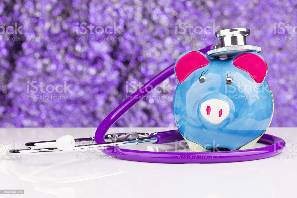 Piggy bank with a stethoscope: health insurance stock photo