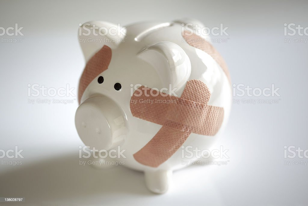 Piggy bank with band aids stock photo