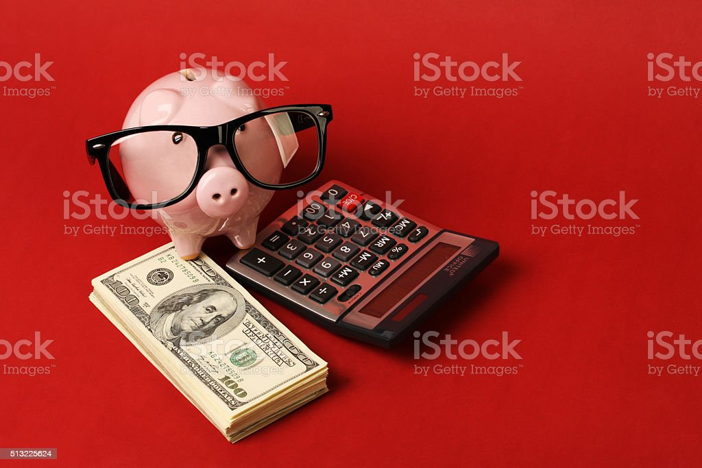 Piggy bank with black spectacle frame of glasses and calculator stock photo