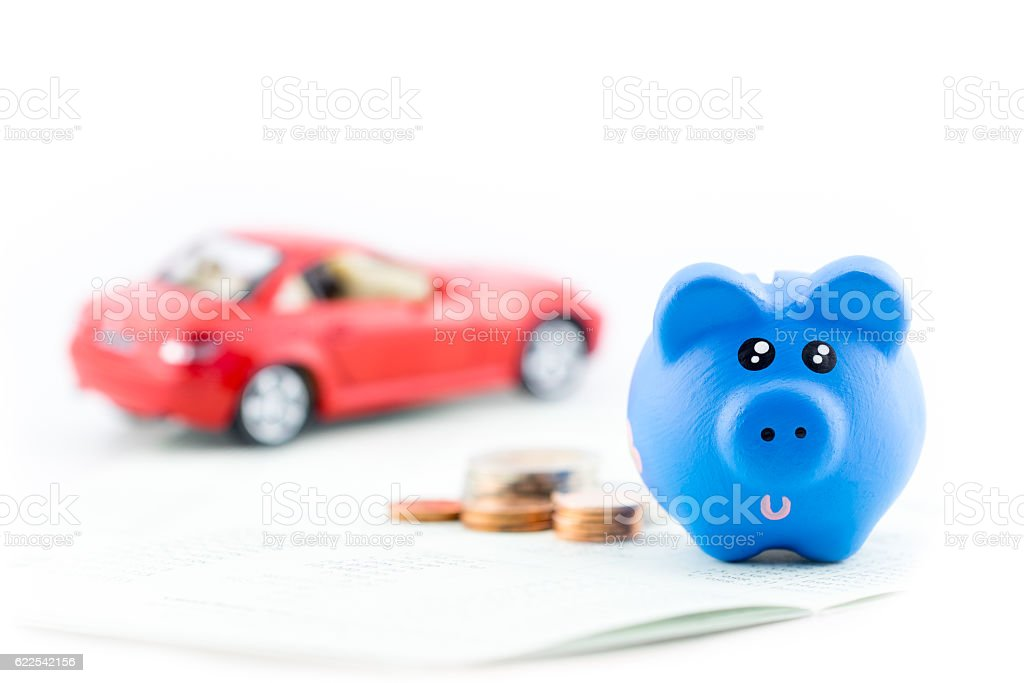 Piggy bank with car toy isolated on white background. stock photo