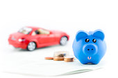 Piggy bank with car toy isolated on white background.