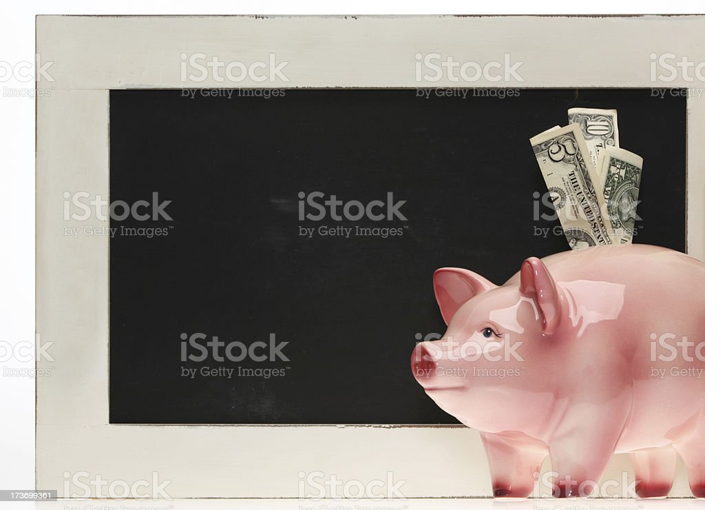 Piggy bank with dollar bills in front of a chalkboard royalty-free stock photo