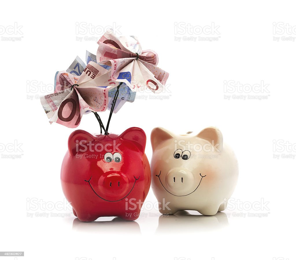 Piggy bank with european currency folded as leaves isolated stock photo