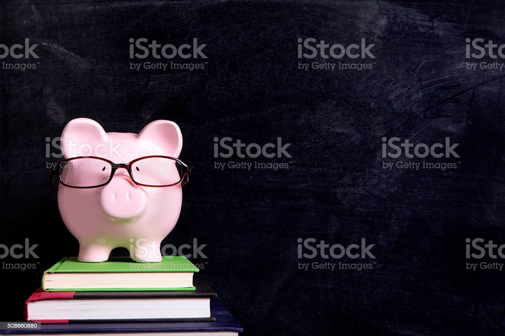 Piggy bank with glasses and blackboard stock photo