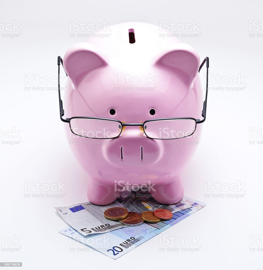 Piggy bank with glasses on Euros royalty-free stock photo
