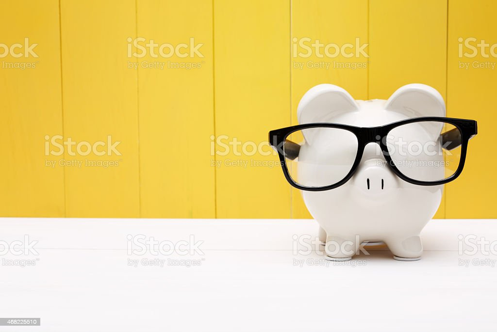 Piggy bank with glasses over yellow wooden wall stock photo