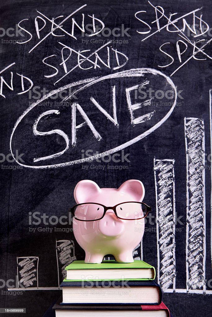 A piggy bank with glasses standing against a savings chart royalty-free stock photo