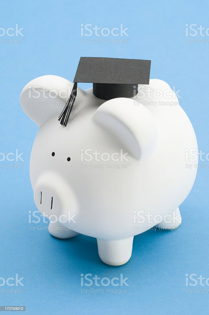 Piggy bank with graduation mortar board-isolated on blue royalty-free stock photo
