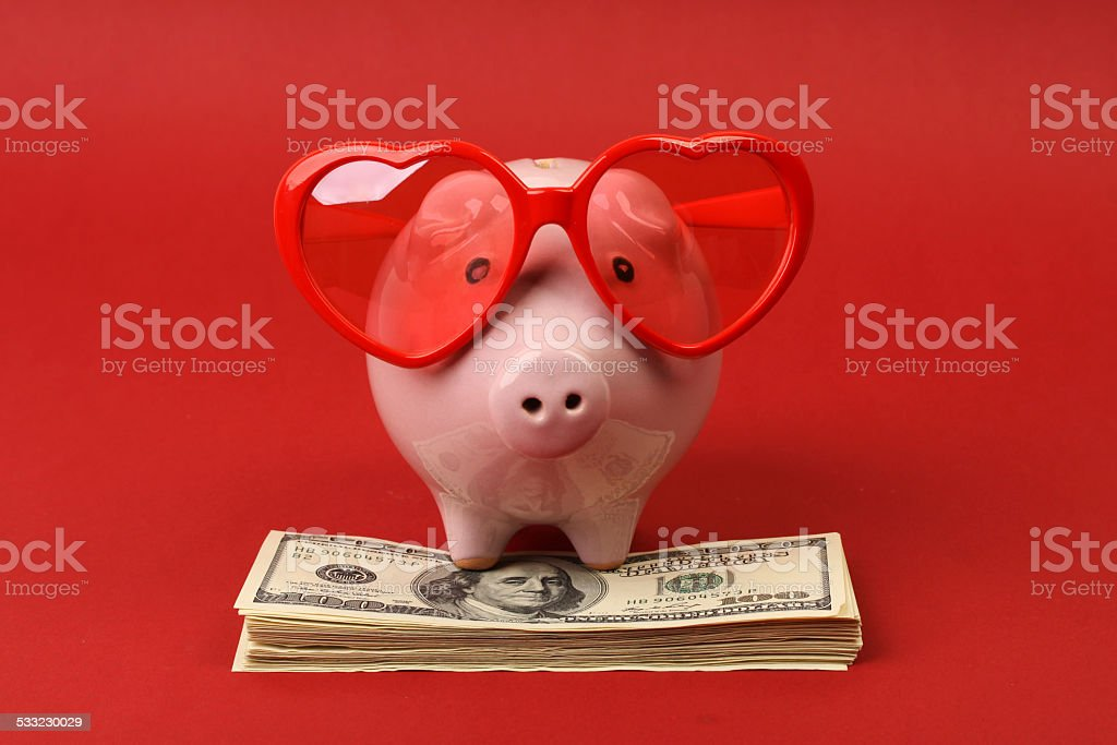 Piggy bank with heart sunglasses standing on stack of money stock photo
