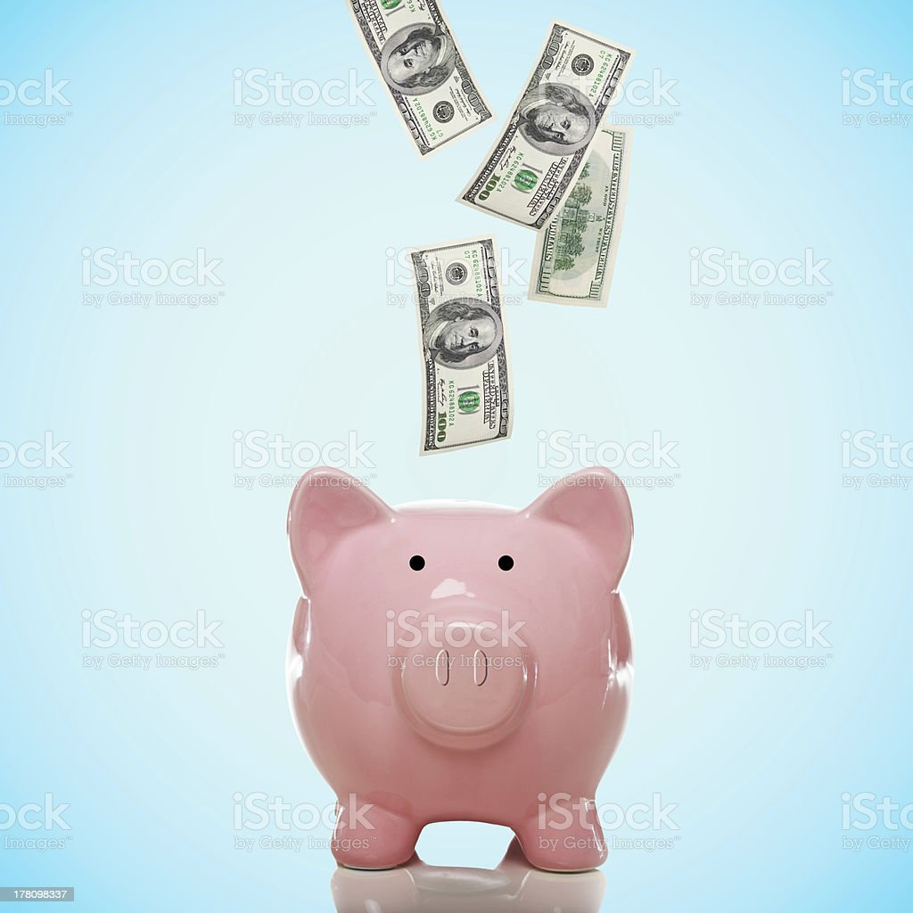 Piggy bank with hundred dollar bills stock photo