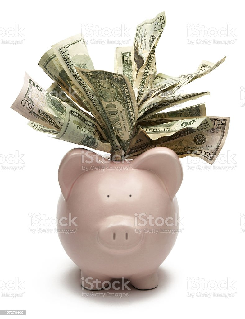 A piggy bank with notes spilling out of the top stock photo