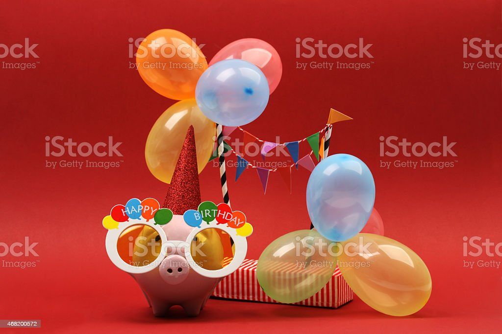 Piggy bank with sunglasses Happy birthday and party balloons stock photo