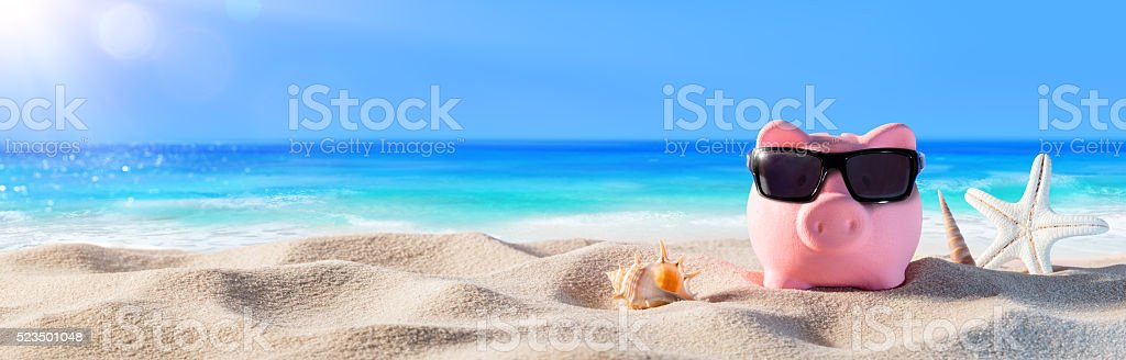 Piggy Bank With Sunglasses On The Beach stock photo