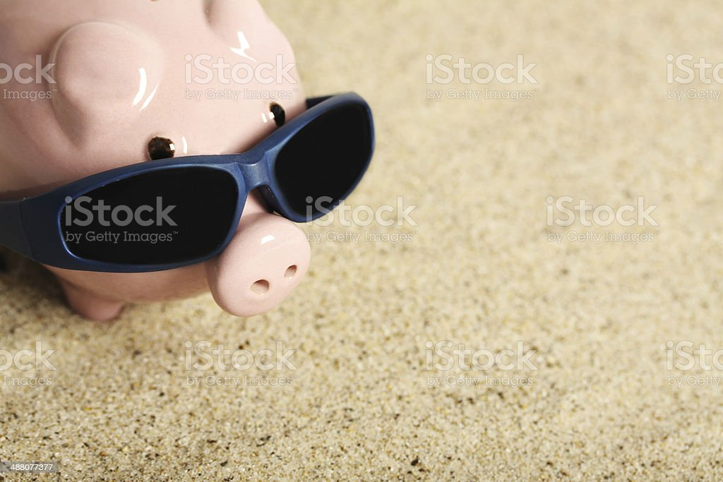 Piggy bank with sunglasses sitting on the sand stock photo