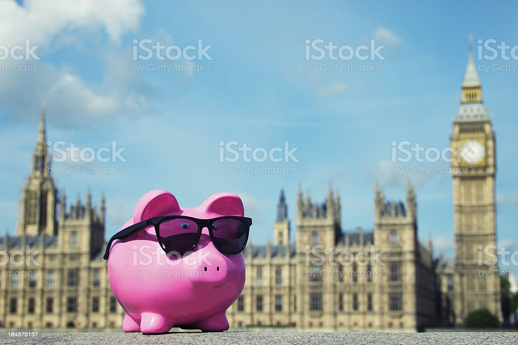 Piggy Bank with Sunglasses Stands at Houses of Parliament royalty-free stock photo
