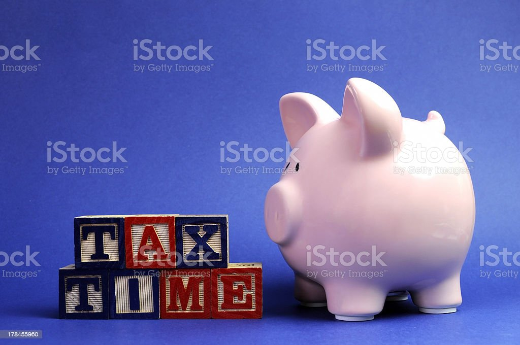 Piggy bank with Tax Time message on building blocks. stock photo