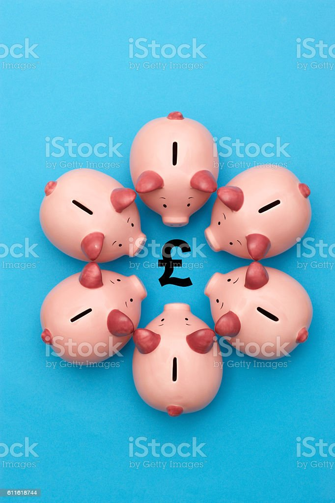 Piggy banks on blue background surrounding a GBP Symbol stock photo